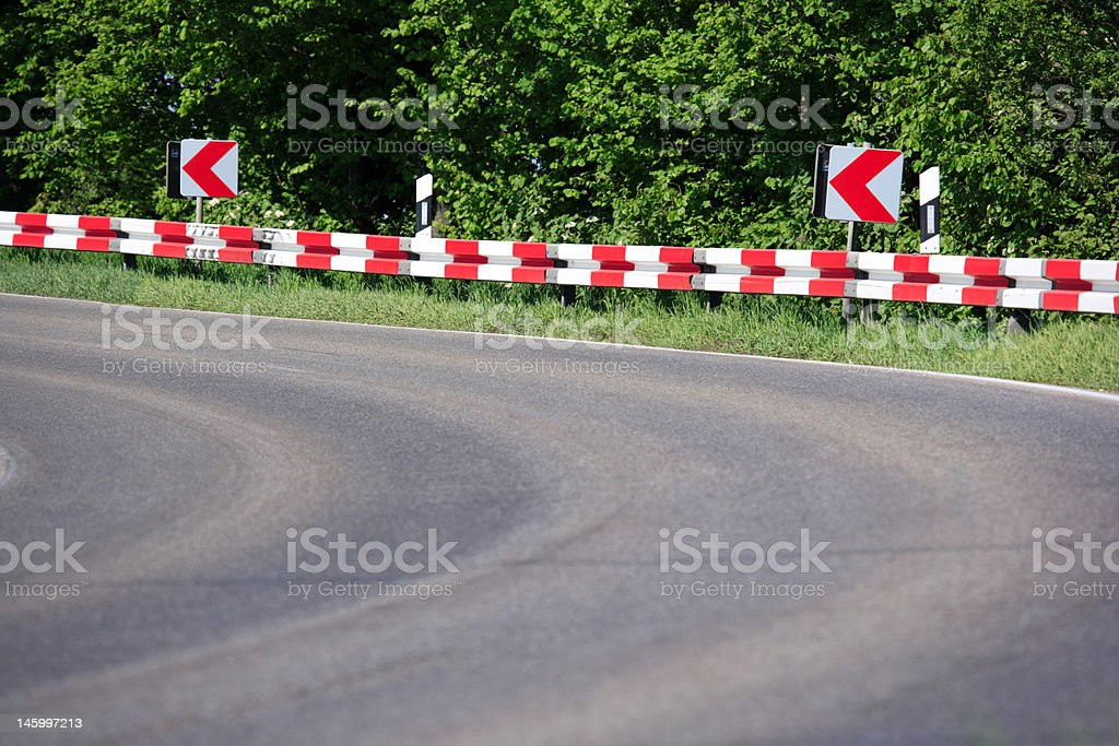 dangerous curve with red and white crash barrier stock photo