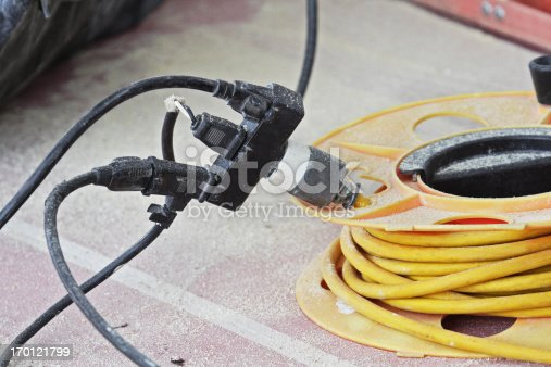 Electric power extension cords. With this mess of a dangerous contraption, a carpenter at a construction site has broken some common sense rules about using electricity safety.