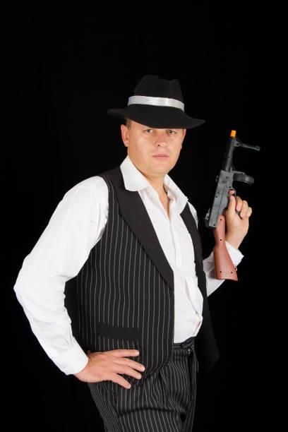 gefährliche gangster mit 1920 stil kleidung stehend mit einer pistole - die wilden 20er stock-fotos und bilder
