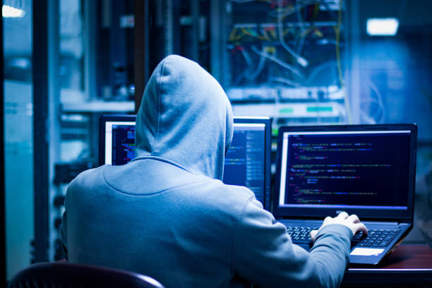 Dangerous hackers hack into corporate servers.They often have multiple data display screens and they hide themselves in darkness. Hackers using laptop computers to penetrate security systems to steal big data from the server room identity theft stock pictures, royalty-free photos & images
