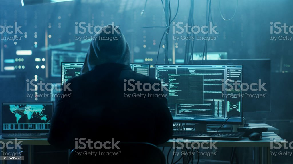 Dangerous Hooded Hacker Breaks into Government Data Servers and Infects Their System with a Virus. His Hideout Place has Dark Atmosphere, Multiple Displays, Cables Everywhere. - Foto stock royalty-free di Adulto