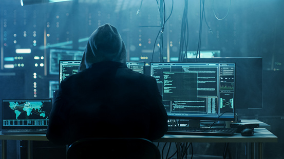 istock Dangerous Hooded Hacker Breaks into Government Data Servers and Infects Their System with a Virus. His Hideout Place has Dark Atmosphere, Multiple Displays, Cables Everywhere. 817486228