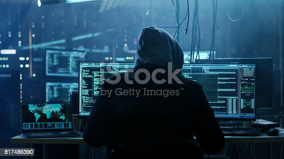 istock Dangerous Hooded Hacker Breaks into Government Data Servers and Infects Their System with a  Virus. His Hideout Place has Dark Atmosphere, Multiple Displays, Cables Everywhere. 817486390