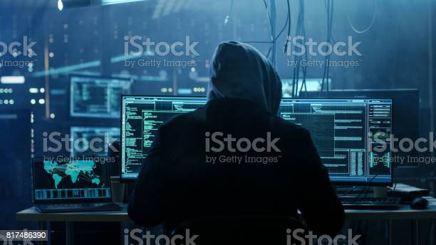 Dangerous Hooded Hacker Breaks Into Government Data Servers And Infects Their System With A Virus His Hideout Place Has Dark Atmosphere Multiple Displays Cables Everywhere Stock Photo - Download Image Now
