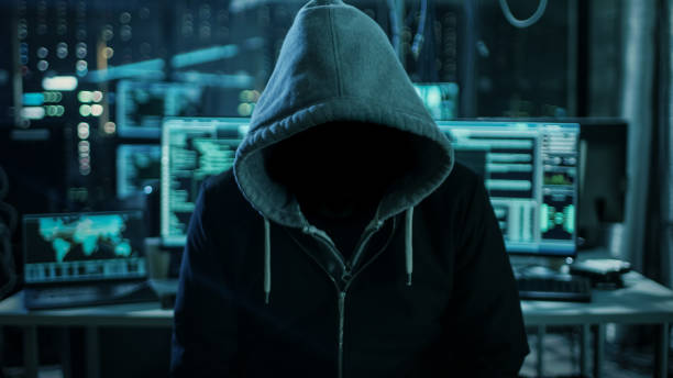 Dangerous Internationally Wanted Hacker Wth Hided Face Looking into the Camera. In the Background His Dark Operating Room with Multiple Displays and Cables. Dangerous Internationally Wanted Hacker Wth Hided Face Looking into the Camera. In the Background His Dark Operating Room with Multiple Displays and Cables. threats stock pictures, royalty-free photos & images