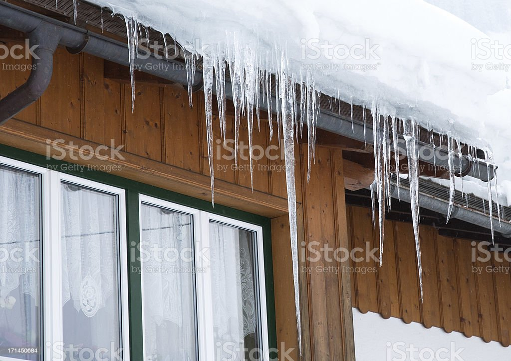 Dangerous large icicle on roof royalty-free stock photo