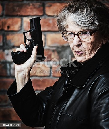A gray-hared senior woman in leather jacket and spectacles glares at camera as she raises her gun in a James Bond pose.