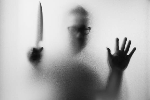 Dangerous man behind the frosted glass with a knife - foto de acervo