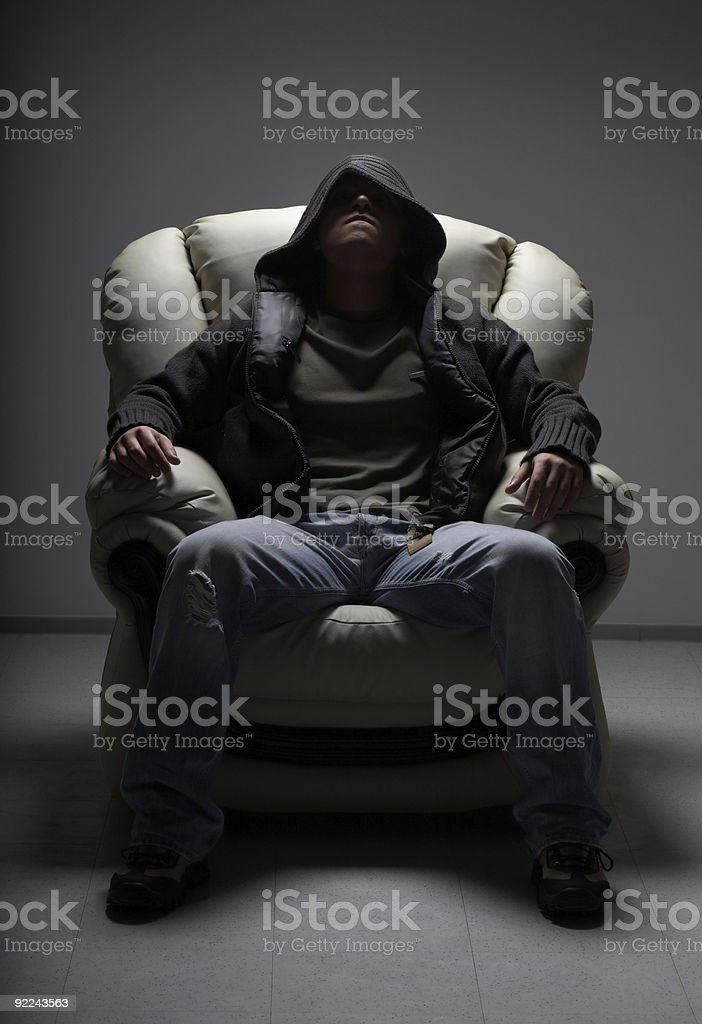 dangerous man sitting in white chair crime, people, anonymity and danger concept -  dangerous man in dark clothes with hood sitting in white chair Adult Stock Photo