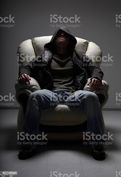 Dangerous Man Sitting In White Chair Stock Photo - Download Image Now