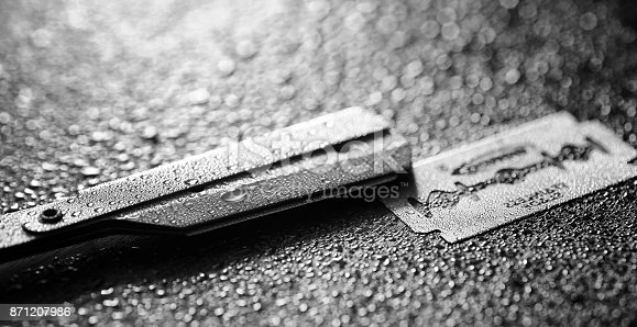 1126324804 istock photo A dangerous razor and a metal blade on the table. Men's shaving 871207986