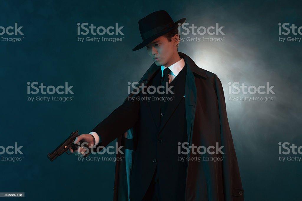 dangerous retro 1940 asian gangster fashion man in long coat stock