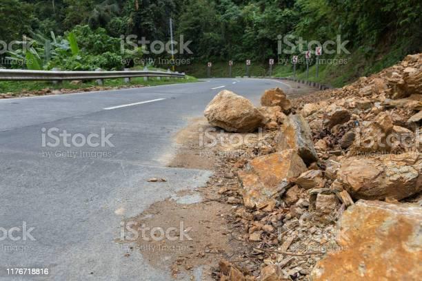 Photo of A dangerous rocky road in a mountainous landslide steep area