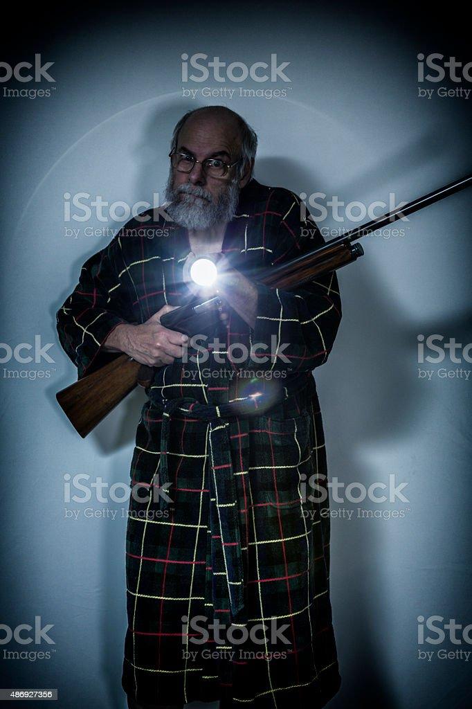 Dangerous Senior Man Holding Shotgun Pointing Flashlight in Dark Basement stock photo