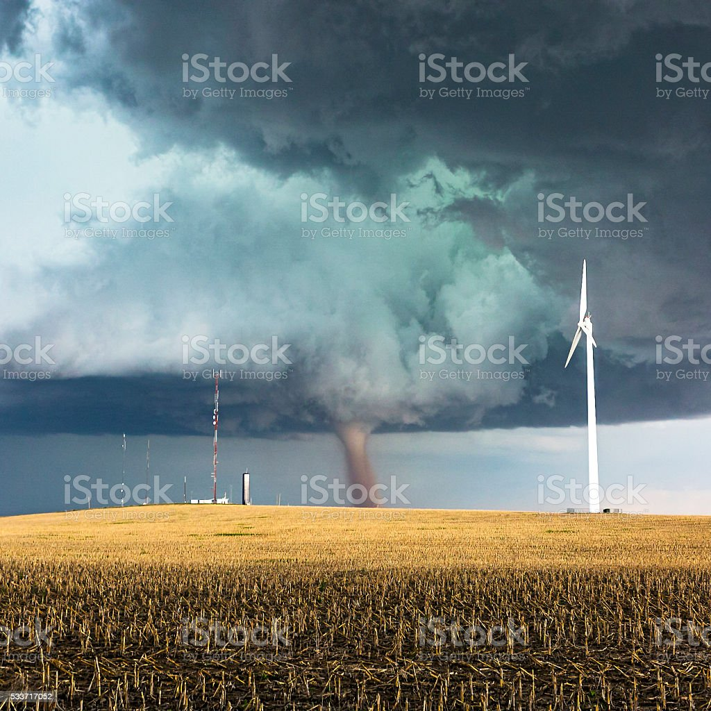 Dangerous tornado with wind generator and telecommunications towers stock photo