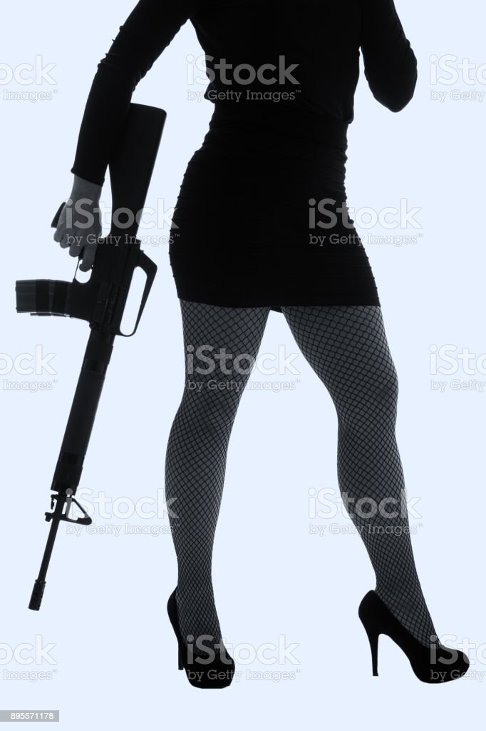 Dangerous woman in black with assault rifle and stylish hat artistic conversion stock photo