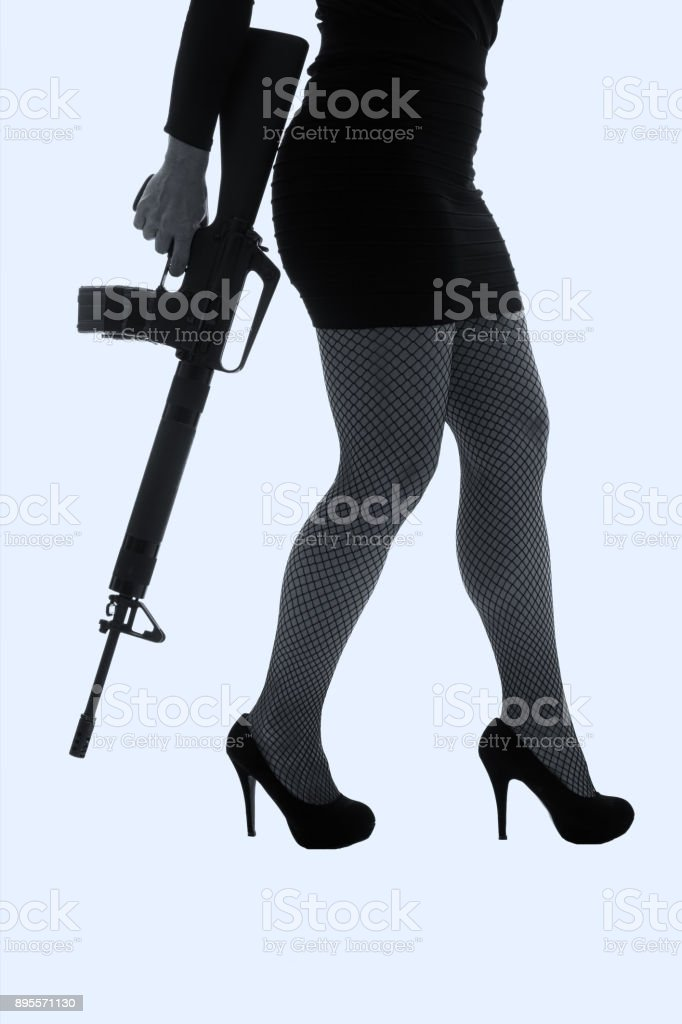 Dangerous woman in black with assault rifle artistic conversion stock photo