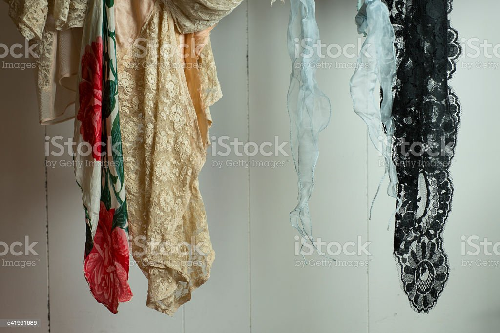 Dangling Assorted Lace Fabric on a White Wooden Background stock photo
