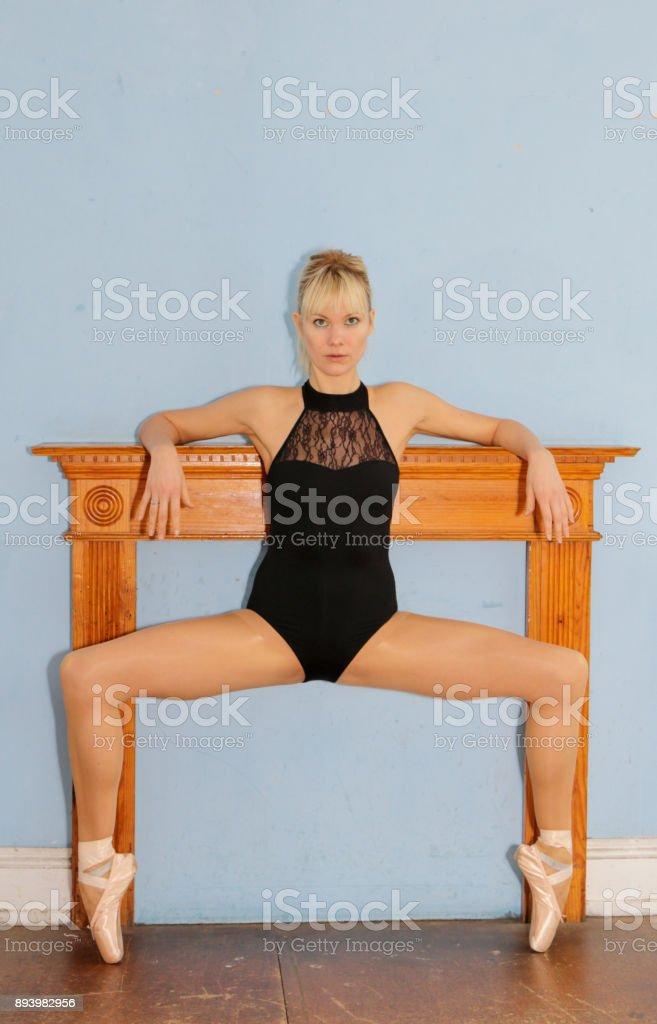 Danish ballerina en pointe before mantel filled in fireplace stock photo