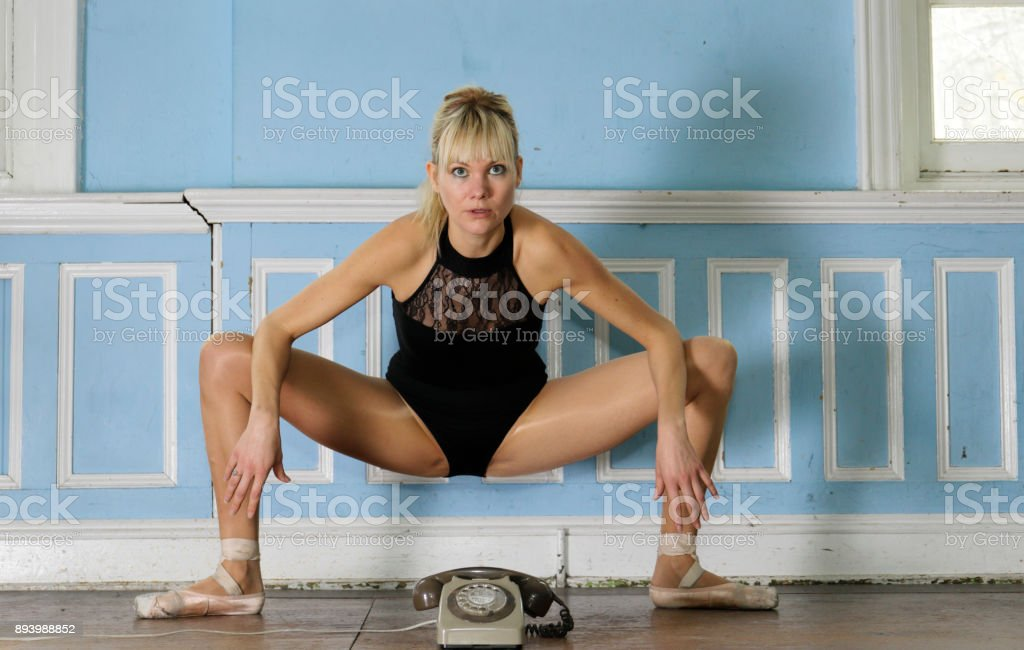 Danish ballerina in athletic pose over an old-fashioned telephone stock photo