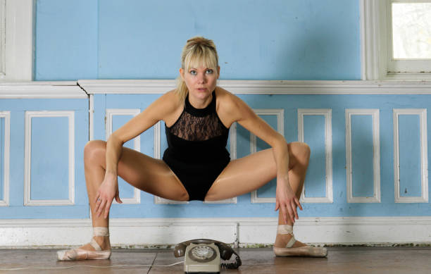 danish ballerina in athletic pose over an old-fashioned telephone - whiteway danish stock photos and pictures