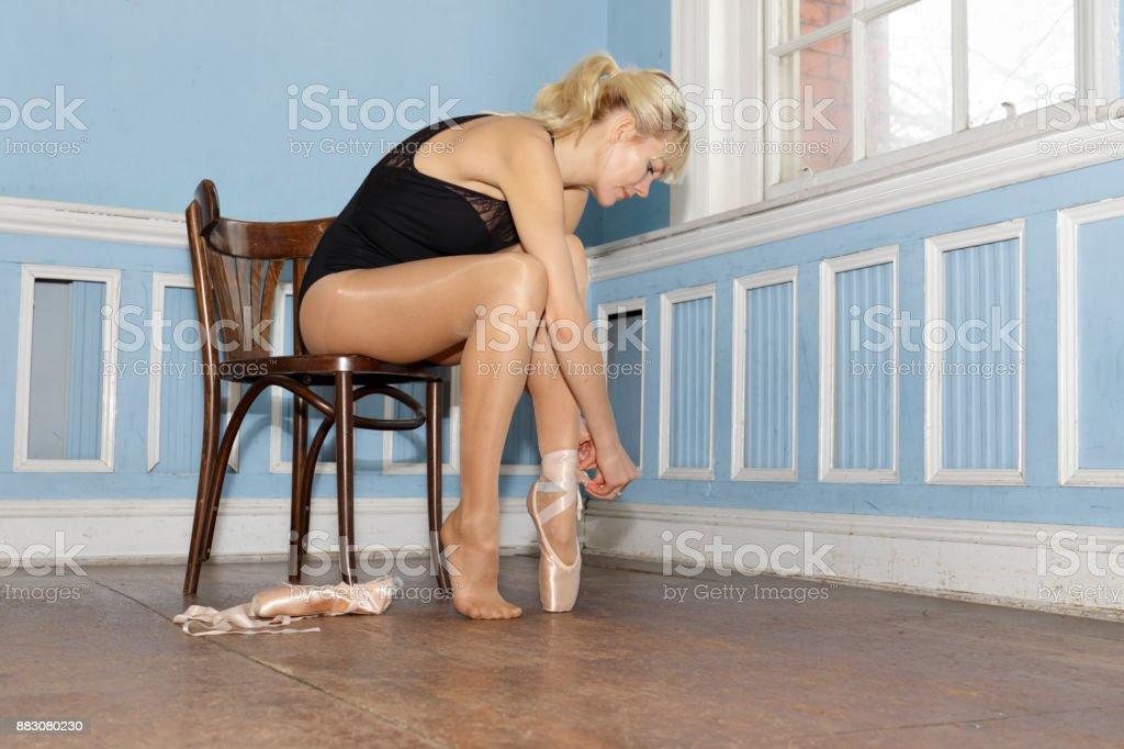 Danish ballerina putting on pointe ballet shoes in old dance studio stock photo