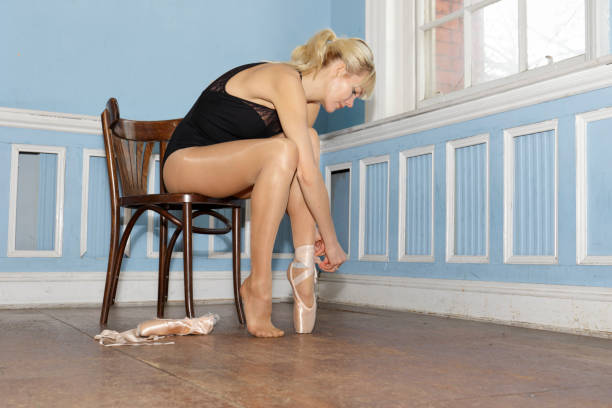 danish ballerina putting on pointe ballet shoes in old dance studio - whiteway danish stock photos and pictures