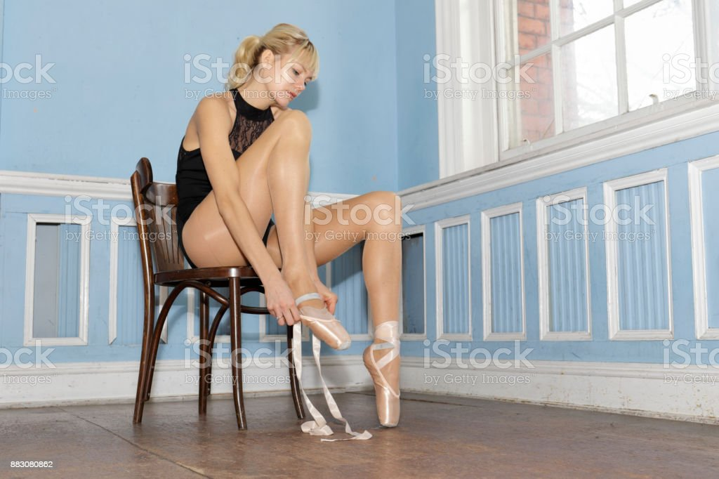 Danish ballerina putting on pointe ballet shoes in old dance studio stock photo