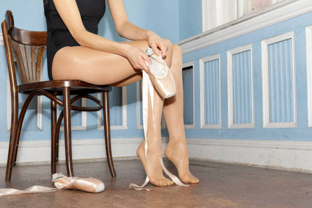 danish ballerina putting on pointe ballet shoes in old dance studio - whiteway ballet stock photos and pictures