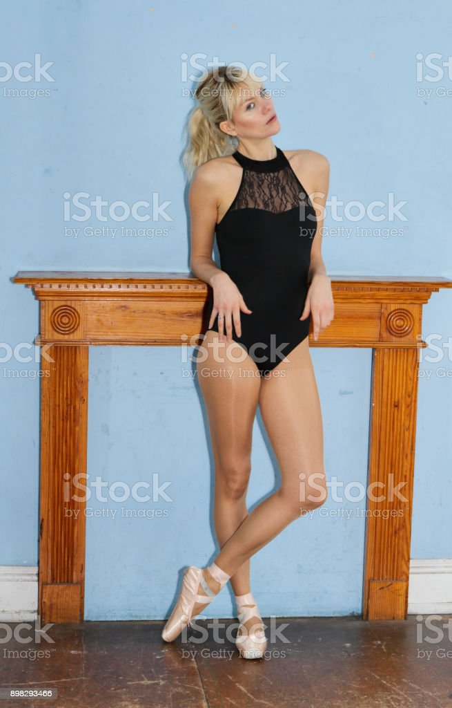Danish ballerina standing relaxed before mantel filled in fireplace stock photo