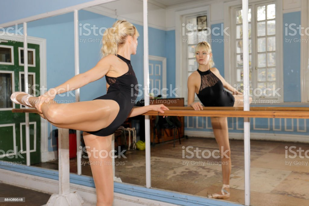 Danish ballerina stretch exercise in front of practise mirror stock photo