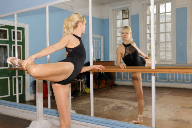 danish ballerina stretch exercise in front of practise mirror - whiteway danish stock photos and pictures