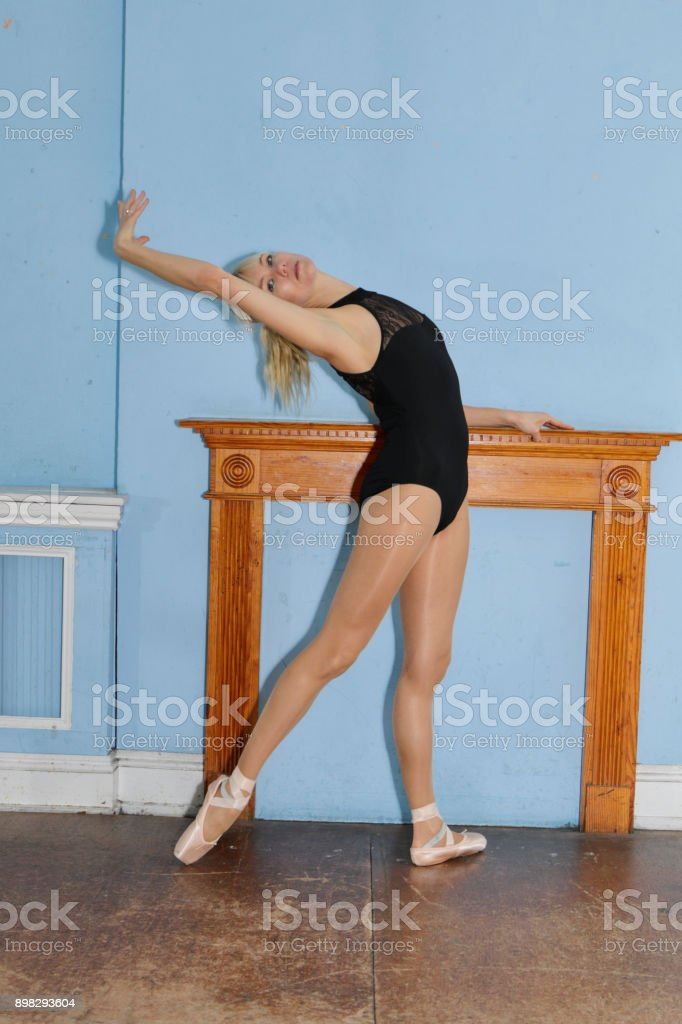 Danish ballerina stretching en pointe before mantel filled in fireplace stock photo