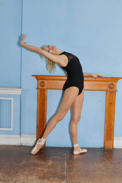 danish ballerina stretching en pointe before mantel filled in fireplace - whiteway danish stock photos and pictures