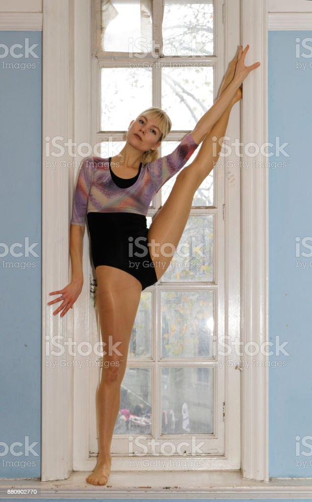 Danish ballerina stretching in old dance studio window London stock photo