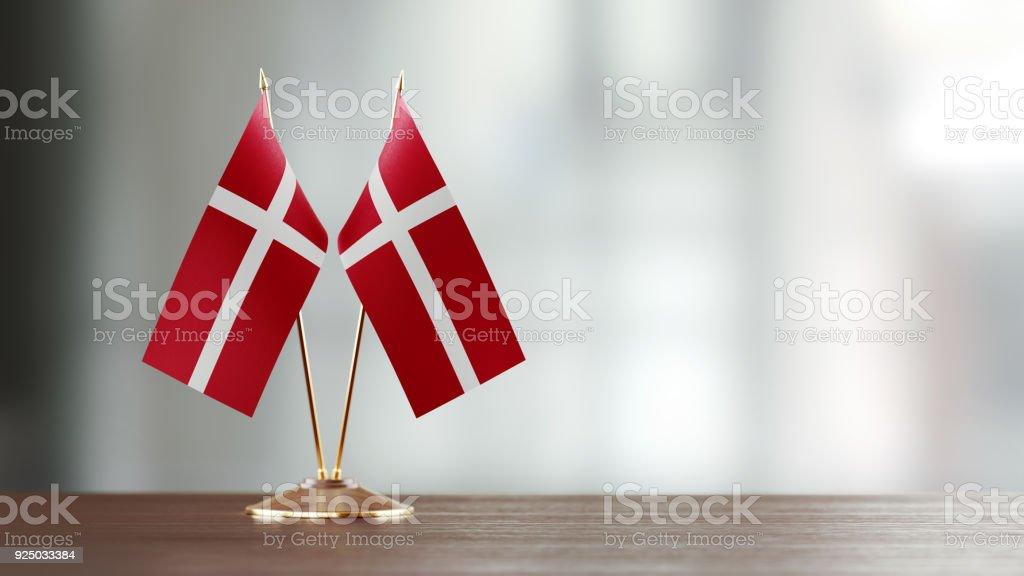 Par de la bandera danesa en un escritorio sobre fondo Defocused - foto de stock