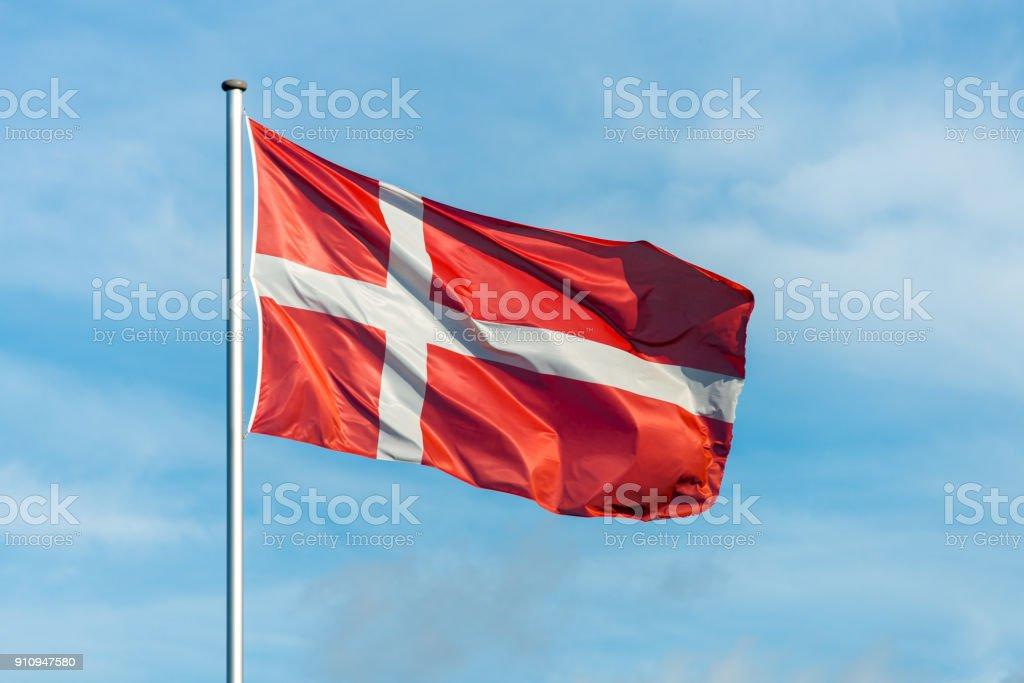 Bandera danesa esquiva en el viento con cielo de fondo - foto de stock
