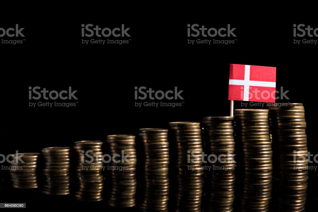 Danish flag with lot of coins isolated on black background stock photo