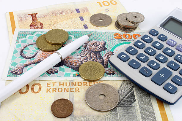Danish Kroner Danish Kroner notes and coins arranged with a calculator and pen to symbolise finance. economic reform stock pictures, royalty-free photos & images
