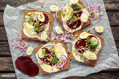 istock Danish open-face rye sandwich with quail eggs, beetroot, pickled onions and cucumbers drizzled with dill 859284764