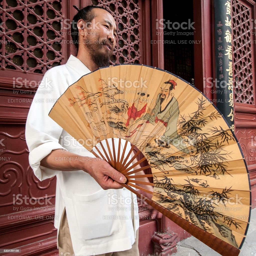 Daoist Monk with teaching scene in a traditional printed fan stock photo
