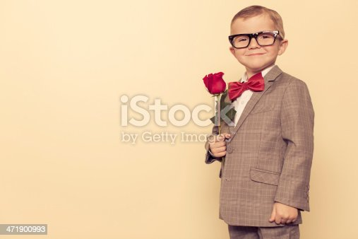 A young boy nerd is in love and ready to show it with a rose.