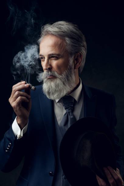 dapper gentleman met mode fotograferen in studio - guy with cigar stockfoto's en -beelden