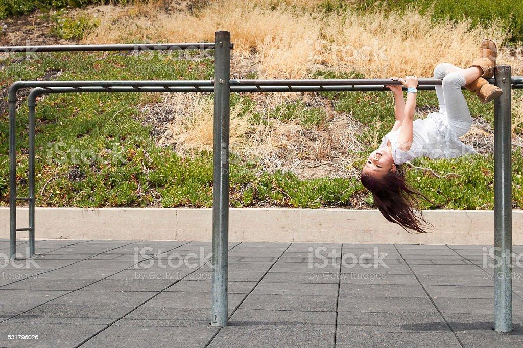 Daring girl hanging upside down on monkey bars stock photo
