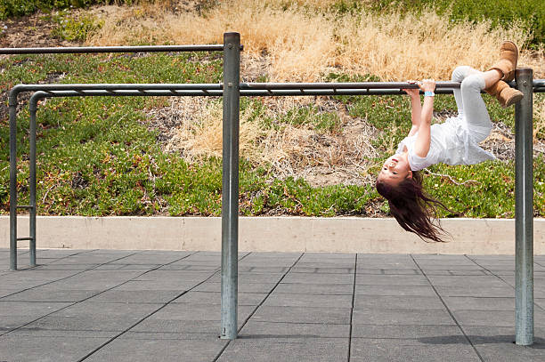 Daring girl hanging upside down on monkey bars stock photo