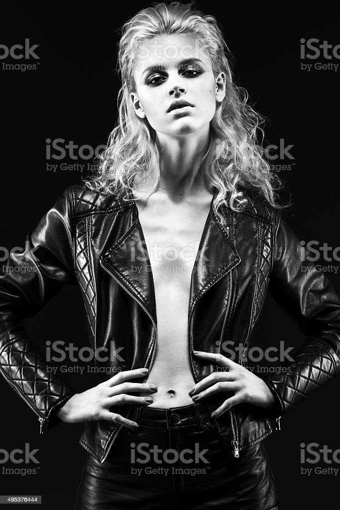 Daring girl model in black leather dress, style of rock stock photo