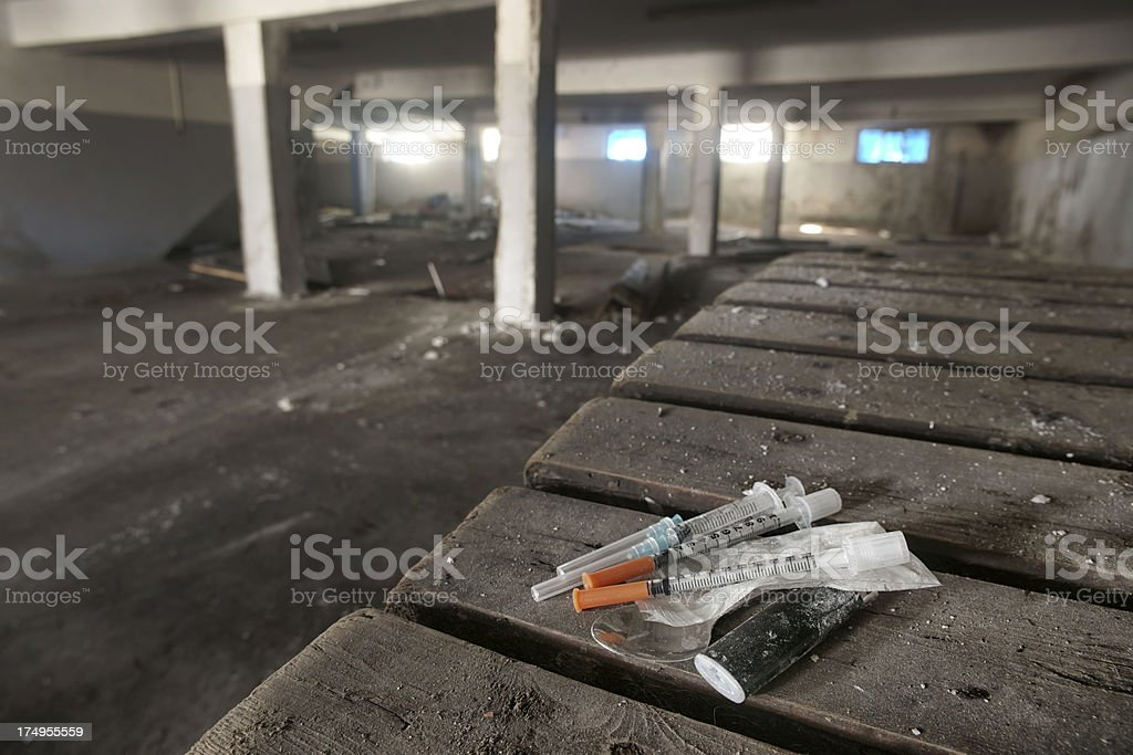 Dark abandoned hall with drugs abuse accessories in foreground stock photo