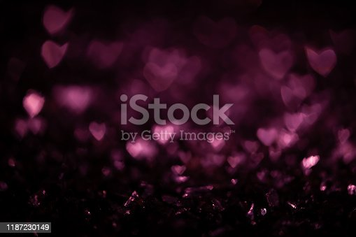 1054573800 istock photo Dark abstract background with pink bokeh defocused lights 1187230149