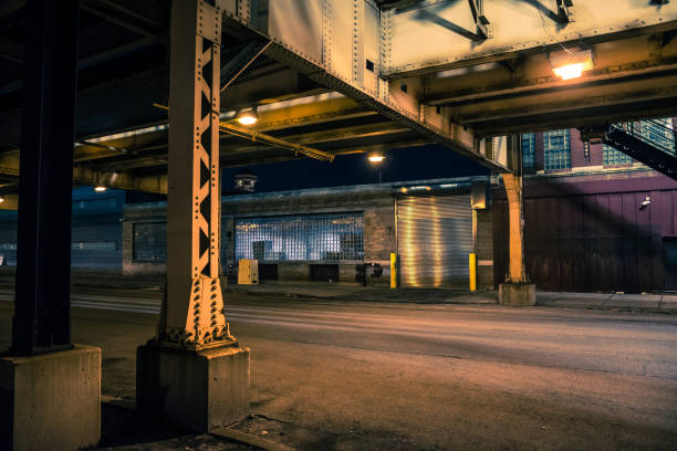 Dark and eerie Chicago urban city street night scenery with elevated CTA train tracks, vintage industrial warehouses and factories. Dark and eerie Chicago urban city street night scenery with elevated CTA train tracks, vintage industrial warehouses and factories. alley stock pictures, royalty-free photos & images