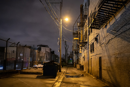 Dark and eerie downtown urban city alley at night in Chicago